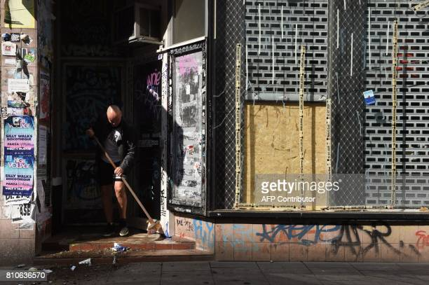 A man sweeps the entrance of a house after riots in Hamburg's Schanzenviertel district on July 8 2017 in Hamburg northern Germany where leaders of...