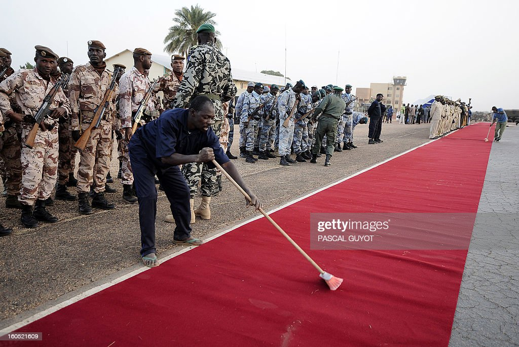 A man sweeps the red carpet before the arrival of France's President and Mali's interim President at the Mopti airport, in Sevare, on February 2, 2013. President Francois Hollande visits today Mali as French-led troops work to secure the last Islamist stronghold in the north after a lightning offensive against the extremists.