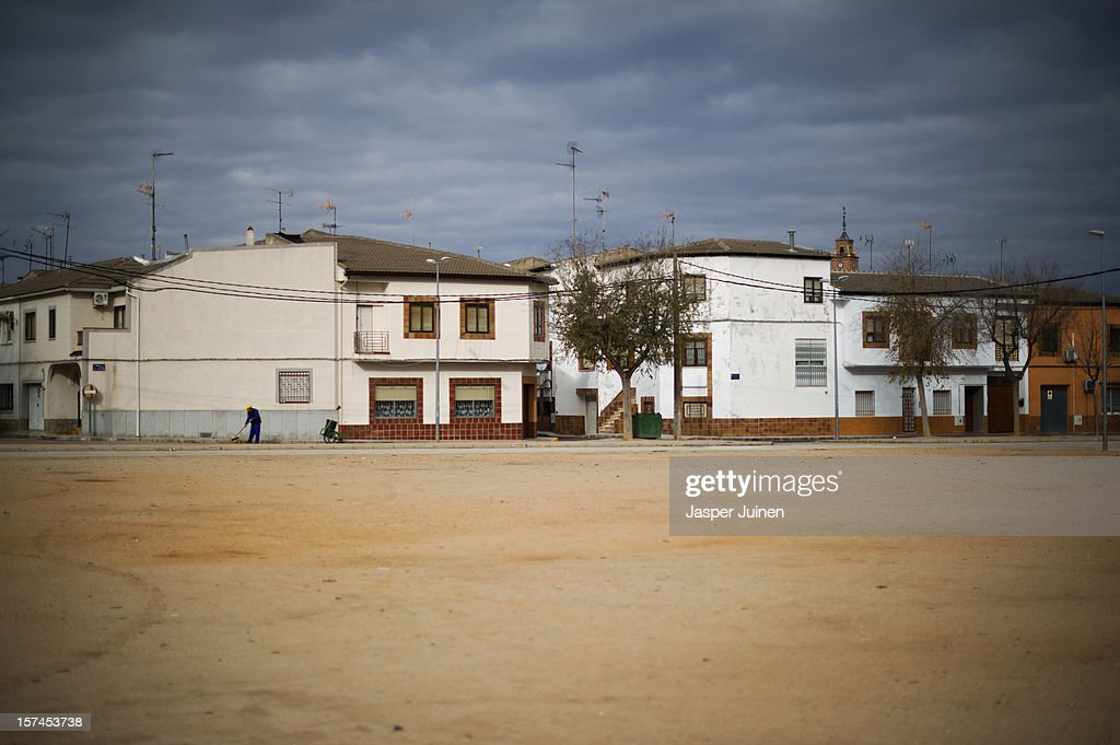 A man sweeps the street on November 30, 2012 in Villacanas, Spain. During the boom years, where in its peak Spain built some 800,000 houses a year accompanied by the manufacturing of millions of wooden doors, the people of Villacanas were part of Spain's middle class enjoying high wages and permanent jobs. During the construction boom years the majority of the doors used within these new developments were made in this small industrial town. Approximately seven million doors a year were once assembled here and the factory employed a workforce of almost 5700 people, but the town is now left almost desolate with the Villacanas industrial park now empty and redundant. With Spain in the grip of recession and the housing bubble burst, Villacanas is typical of many former buoyant industrial Spanish towns now struggling with huge unemployment problems.