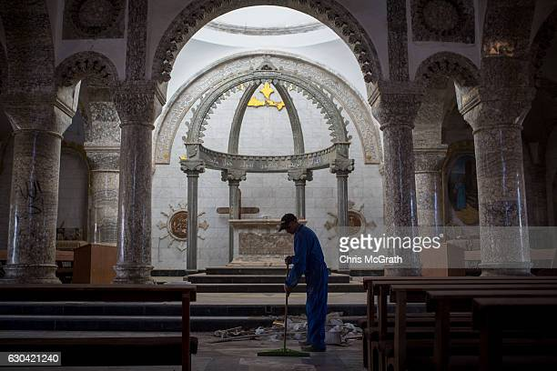 A man sweeps up rubble in preparation for the Christmas Day mass at the Mar Hanna Church on December 22 2016 in Mosul Iraq After recently being...