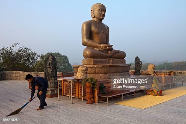 A man sweeps whilst a woman prays at dawn at the statue of Lord Mahavira at the Ahinsa Sthal Jain temple Delhi India