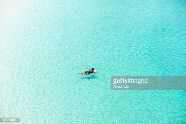 Man Swimming   at Pink Beach - The most beautiful beach in Komodo National Park - Labuan Bajo in Flores Island- East Nusa Tenggara - Indonesia