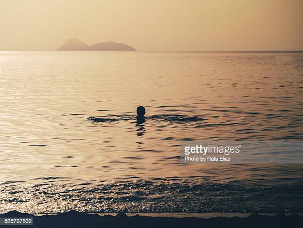 Man swimming in sea at sunset