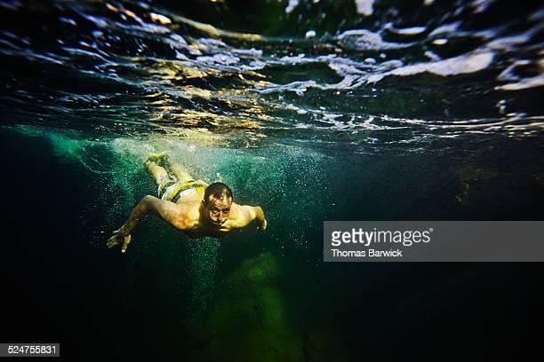 Man swimming underwater in river underwater view