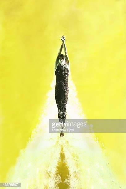 Man swimming underwater on yellow background