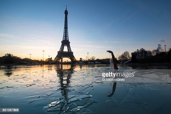 TOPSHOT A man swims in the frozen water of the Trocadero fountain in front Eiffel Tower on January 6 2017 in Paris / AFP / OLIVIER MORIN