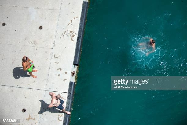 A man swims near the Museum of European and Mediterranean Civilisations in the Vieux Port in Marseille southern France on August 2 2017 as a heatwave...