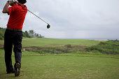 Man swinging golf club, rear view