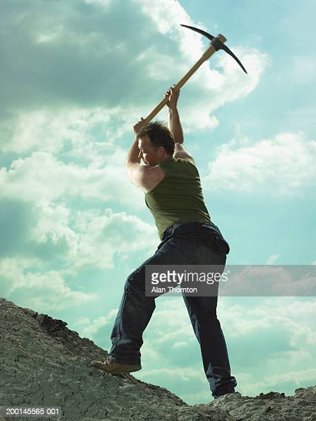 Man swinging pick axe on mound of clay, low angle view