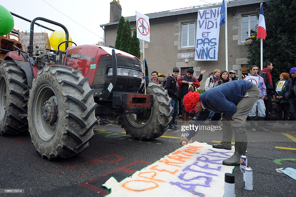 A man tags ''Operation Asterix'' on a banner during a demonstration against a project to build an international airport on November 17, 2012 in Notre-Dame-des-Landes, western France. The project was signed in 2010 and the international airport is supposed to open in 2017 near the city of Nantes.