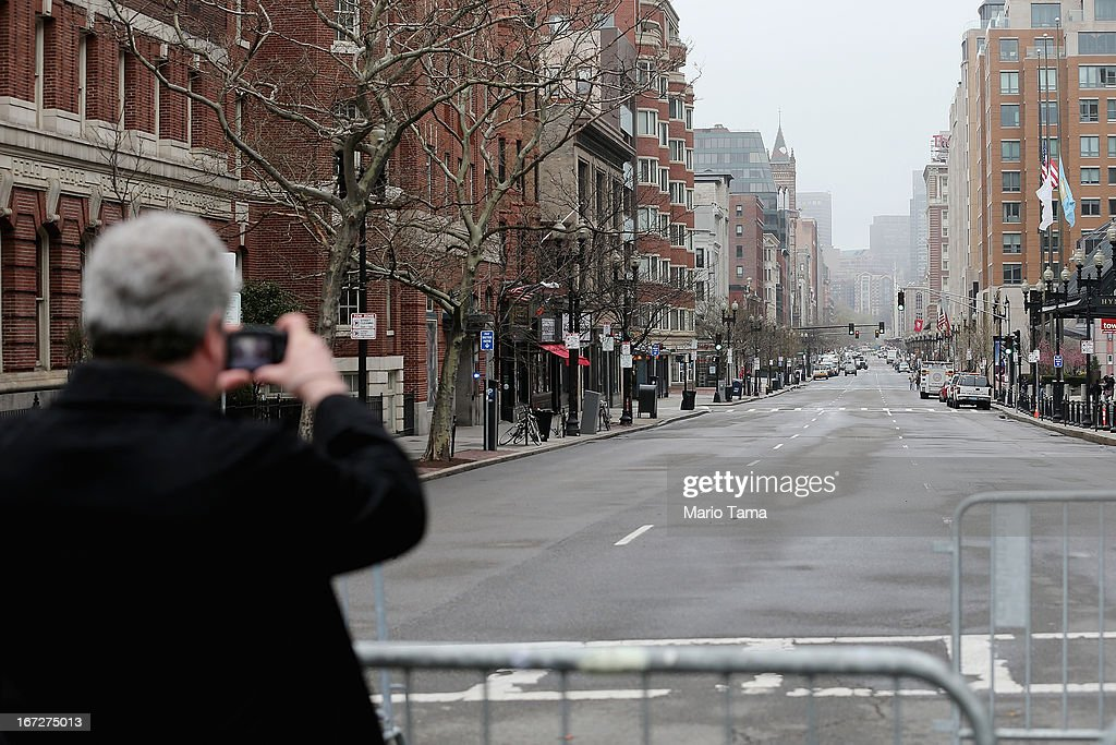 A man take photos at a barricade blocking a still closed section of Boylston Street near the site of the Boston Marathon bombings on April 23, 2013 in Boston, Massachusetts. Business owners and residents of the closed section were allowed to return to their properties today while under escort of city staff.