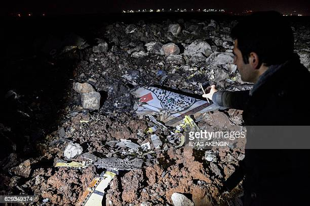 A man take photos of pieces of crashed Turkish F16 war plane on December 12 2016 in the southeastern city of Diyarbakir A Turkish fighter jet crashed...