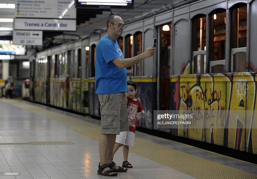 A man take pictures of the historic wagons of La Brugeoise of the subway Line A which is expected to be close soon following a decision by city mayor Mauricio Macri to replace the fleet with Chinese-made wagons, in Buenos Aires, on December 29, 2012. Line A was the first subway line to work in the southern hemisphere and its trains are among the ten oldest still working daily. The La Brugeoise wagons were constructed between 1912 and 1919 by La Brugeoise et Nicaise et Delcuve in Belgium. AFP PHOTO / ALEJANDRO PAGNI