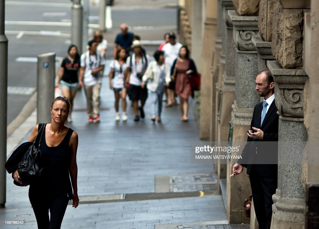 A man (R) takes a break outside an office-building on a busy market street in Sydney on December 28, 2012. Australia posted a surprise drop in unemployment to 5.2 percent in early December, despite data showing the mining-powered economy is cooling due to China's slowdown.