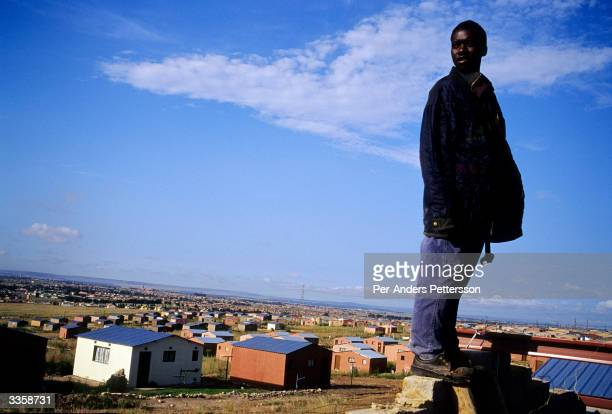 A man takes a break while working on the roof of a RDP government sponsored house also known as Mandela houses on February 19 2004 in Soweto outside...