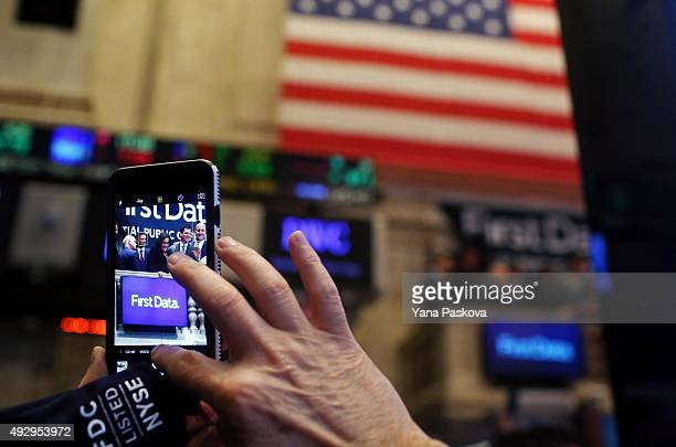 A man takes a cell phone pictures of First Data Corporation CEO Frank Bisignano after he rings the opening bell at the New York Stock Exchange to...