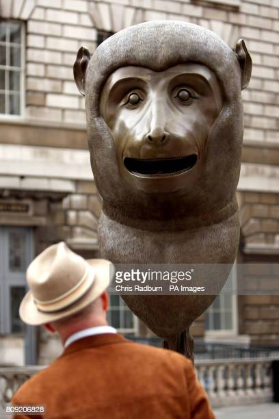 A man takes a closer look at Ai Weiwei's first outdoor sculpture to go on display in London 'Circle of Animals/Zodiac Heads' in the historic...