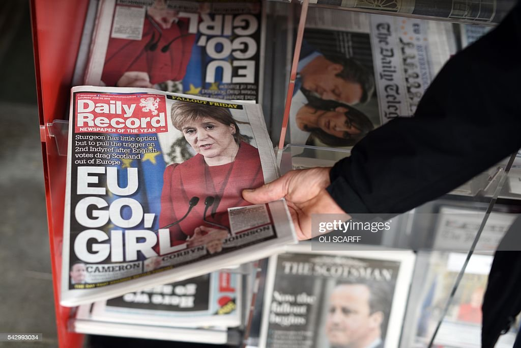 A man takes a copy of the Daily Record newspaper reporting on the pro-Brexit result of the UK's EU referendum vote and with an image of Scotland's First Minister and Leader of the Scottish National Party (SNP), Nicola Sturgeon, in a store in Edinburgh, Scotland on June 25, 2016. The result of Britain's June 23 referendum vote to leave the European Union (EU) has pitted parents against children, cities against rural areas, north against south and university graduates against those with fewer qualifications. London, Scotland and Northern Ireland voted to remain in the EU but Wales and large swathes of England, particularly former industrial hubs in the north with many disaffected workers, backed a Brexit. / AFP / OLI