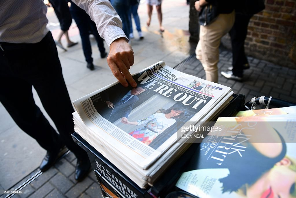 A man takes a copy of the London Evening Standard with the front page reporting the resignation of British Prime Minister David Cameron and the vote to leave the EU in a referendum, showing a pictured of Cameron holding hands with his wife Samantha as they come out from 10 Downing Street, in London on June 24, 2016. Britain voted to break away from the European Union on June 24, toppling Prime Minister David Cameron and dealing a thunderous blow to the 60-year-old bloc that sent world markets plunging. / AFP / LEON