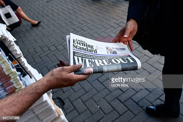 A man takes a copy of the London Evening Standard with the front page reporting the resignation of British Prime Minister David Cameron and the vote...