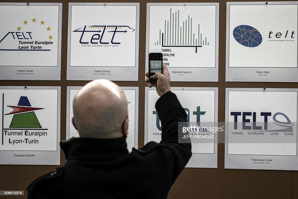 A man takes a cpiture of the new logo (2nd R, top row) for the TELT (Tunnel Euralpin Lyon Turin), a TGV high speed train rail line project connecting Lyon and Turin, on February 8, 2016, in the Confluence museum in Lyon, central-eastern France, during an award ceremony to choose the new logo. / AFP / JEFF PACHOUD