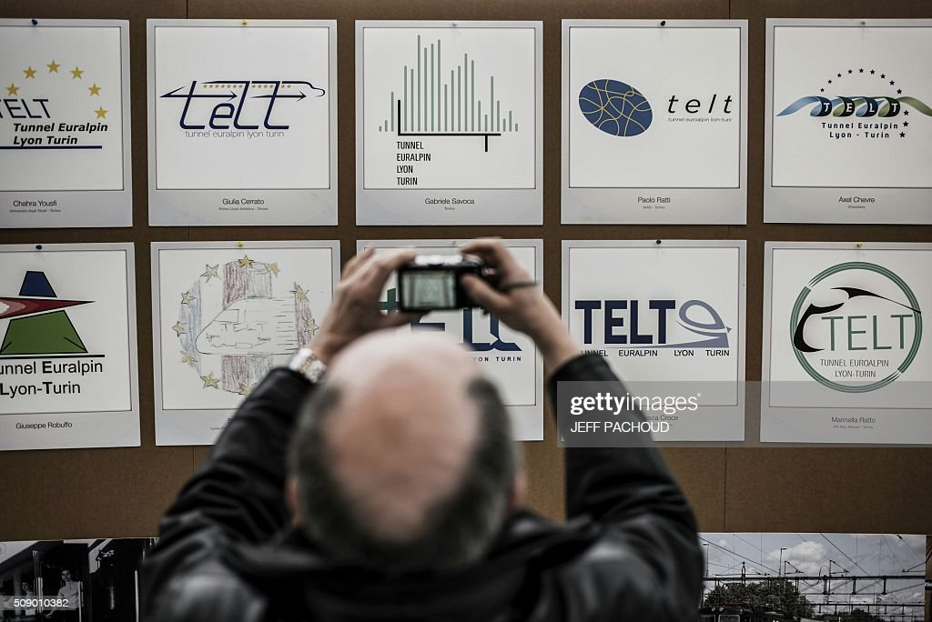A man takes a cpiture of the new logo (C, top row) for the TELT (Tunnel Euralpin Lyon Turin), a TGV high speed train rail line project connecting Lyon and Turin, on February 8, 2016, in the Confluence museum in Lyon, central-eastern France, during an award ceremony to choose the new logo. / AFP / JEFF PACHOUD