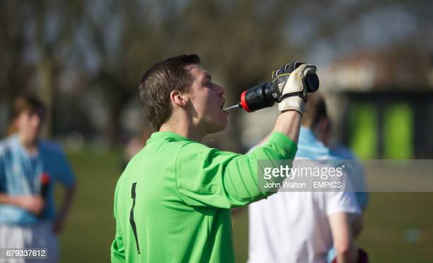 A man takes a drink during a break in play during a league match between Boleyn FC and Cranham