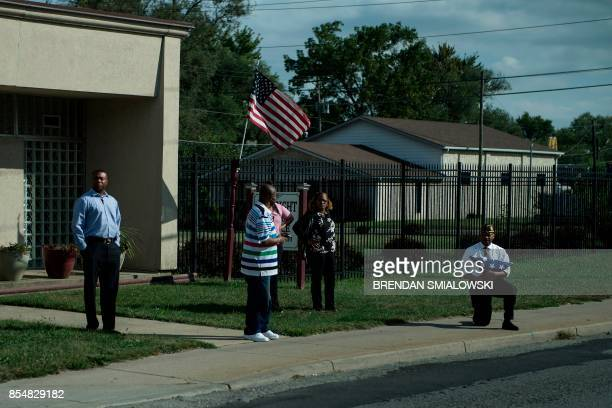 A man takes a knee while holding an American flag as a motorcade with US President Donald Trump drives to Indianapolis International Airport...