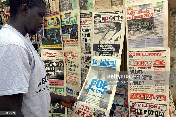 A man takes a look at frontpages of Cameroonese newspapers titling about the death of soccer midfielder MarcVivien Foe's 02 July 2003 in a street of...
