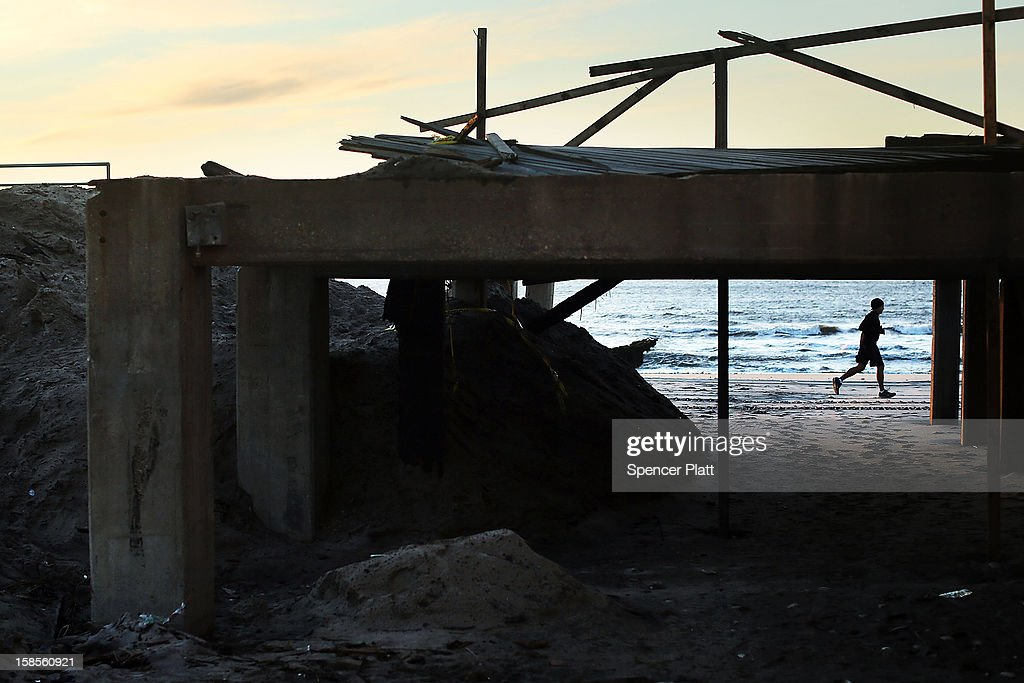 A man takes a morning run on the beach near the heavily damaged boardwalk in the Rockaway neighborhood on November 19, 2012 in the Queens borough of New York City. As the holidays approach after Superstorm Sandy slammed into parts of New York and New Jersey, thousands of residents and businesses are still recovering from the devastation.