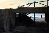 A man takes a morning run on the beach near the heavily damaged boardwalk in the Rockaway neighborhood on November 19 2012 in the Queens borough of...