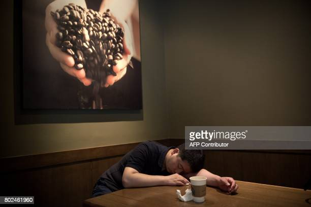 A man takes a nap after drinking a coffee inside a Starbucks in Beijing on June 28 2017 / AFP PHOTO / NICOLAS ASFOURI