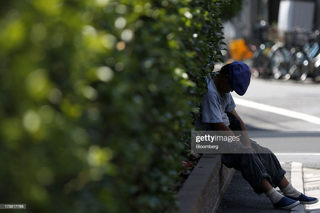 A man takes a nap against shrubs outside a park in Tokyo, Japan, on Monday, July 8, 2013. The number of Japanese seniors living alone will rise 54 percent to 7.17 million in 2030 from 4.66 million in 2010, according to the National Institute of Population and Social Security Research, set up by the Ministry of Health, Labour and Welfare. To manage the costs stemming from the aging society, the government aims to push back the pension age to 65 from 60 in stages through 2025. Photographer: Kiyoshi Ota/Bloomberg via Getty Images