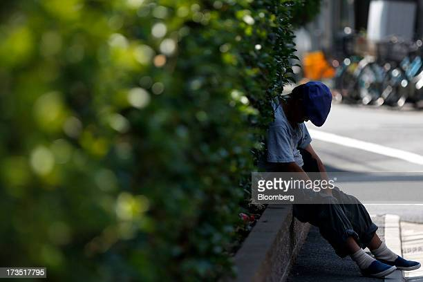 A man takes a nap against shrubs outside a park in Tokyo Japan on Monday July 8 2013 The number of Japanese seniors living alone will rise 54 percent...