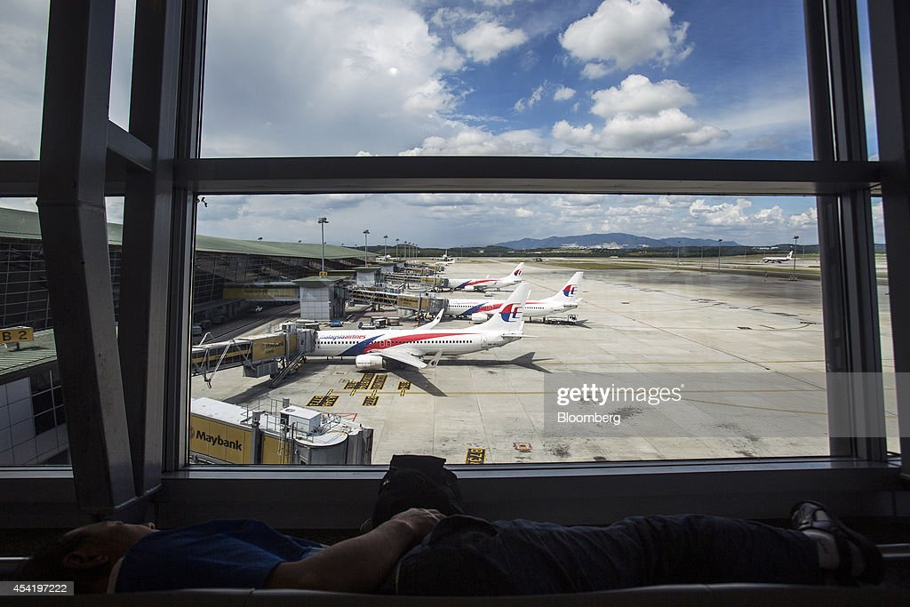 A man takes a nap as aircraft operated by Malaysian Airline System Bhd. (MAS) stand on the tarmac at Kuala Lumpur International Airport (KLIA) in Sepang, Malaysia, on Tuesday, Aug. 26, 2014. Malaysia Airlines are scheduled to release second quarter earnings Aug. 27 as the airline considers job cuts, a review of aircraft orders and replacing its chief executive officer after the national carrier suffered two disasters this year, people familiar with the plan said. Photographer: Charles Pertwee/Bloomberg via Getty Images