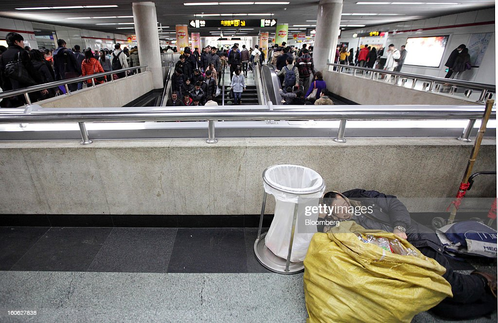A man takes a nap as passengers exit a connecting subway station at Shanghai Railway Station in Shanghai, China, on Sunday, Feb. 3, 2013. Forecasts of snow and rain across China threaten to disrupt the travel plans of millions of Chinese heading home for the Lunar New Year holidays that start Feb. 9, the national weather agency warned. Photographer: Tomohiro Ohsumi/Bloomberg via Getty Images