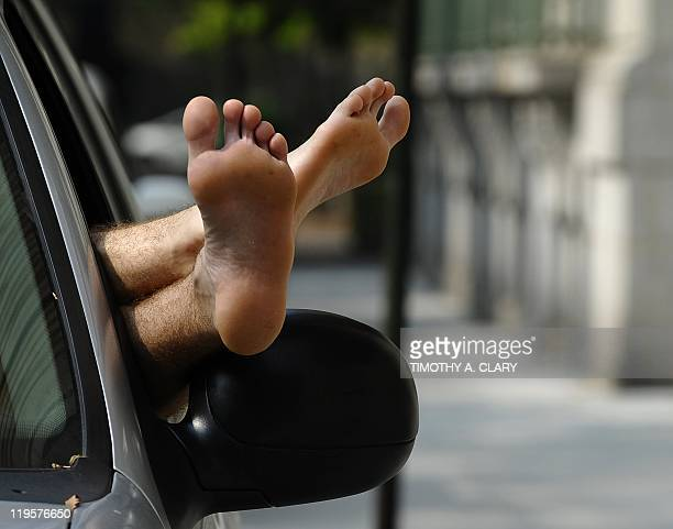 A man takes a nap in his car on the Upper east Side of New York City on July 21 2011 as people try different ways to beat the hot weather Heat...