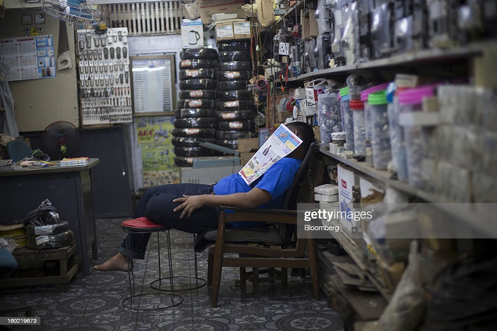 A man takes a nap inside a hardware store in Yangon, Myanmar, on Tuesday, Jan. 22, 2013. Myanmar cleared about $1 billion in overdue debt with the Asian Development Bank and World Bank using a bridge loan from Japan, opening the door for increased lending as the country seeks to overhaul its infrastructure. Photographer: Brent Lewin/Bloomberg via Getty Images