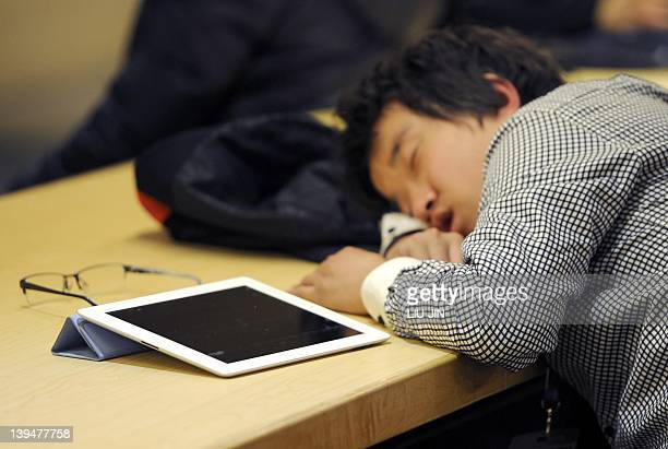 A man takes a nap next to his Ipad at a cafe shop in Beijing on February 22 2012 A trademark dispute between Apple and a Chinese computer maker moved...