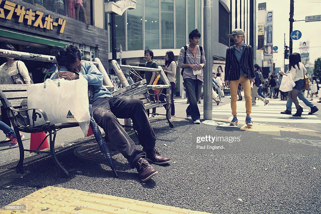 CONTENT] A man takes a nap on a street side bench in Tokyo's Harajuku Fashion District