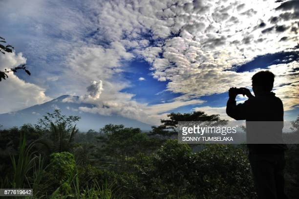 TOPSHOT A man takes a photo as a puff of smoke comes from Mount Agung volcano taken from the Rendang subdistrict in Karangasem Regency on Indonesia's...