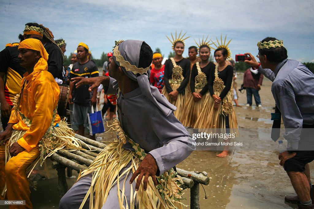 A man takes a photo (R) as a shaman of the Mah Meri tribe performs prayers on the beach as they offer a prayer to the sea at Pulau Carey, Straits of Malacca beach on February 12, 2016 in Pulau Carey, Malaysia. Every year, the indigenous people of Mah Meri village, located in Pulau Carey, about 140 km (87 miles) southwest of Kuala Lumpur, perform the 'Puja Pantai' ritual prayer and 'Main Jo-oh' dance to appease the spirits of the seas and celebrate the New Year.