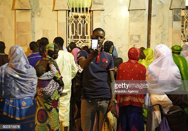 A man takes a photo as the people gather at the Serigne Mbaye Sy Mosque for the Mawlid al Nabi ceremony marking the birth of the Prophet Muhammad...