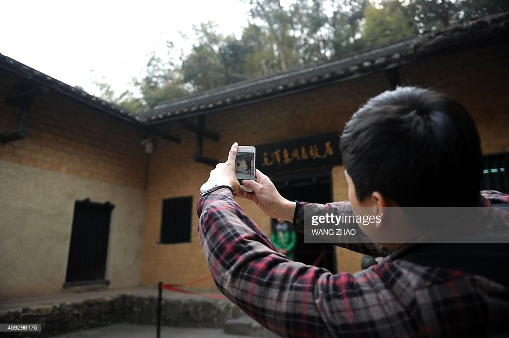A man takes a photo at the former residence of former Chinese leader Mao Zedong in Shaoshan, in China's central province of Hunan on December 25, 2013. Thousands of admirers of Communist China's founder Mao Zedong flocked to his home town on December 25 to bow before his graven image -- including one statue of solid gold -- before the 120th anniversary of his birth.