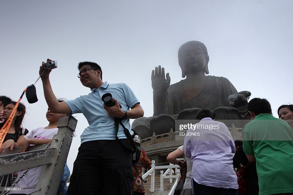 A man takes a photo before the Tian Tan Buddha statue, also known as the Big Buddha, on Lantau island in Hong Kong on May 21, 2010. Buddhists throughout Asia are celebrating the birthday of Siddhartha Gautama, the spiritual teacher who founded Buddhism. Hong Kong's Big Buddha statue was until 2007 the tallest of its kind, standing 34 metres (112 feet) tall.