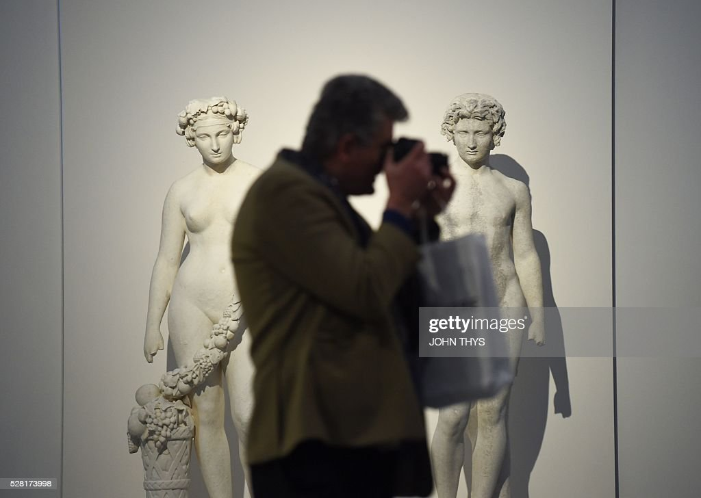 A man takes a photo during the inauguration of the La Boverie museum on May 4, 2016 in Liege. The new museum La Boverie was inaugurated today, with the exhibition 'En Plein Air' (In The Open Air) organised in partnership with Le Louvre museum. / AFP / JOHN