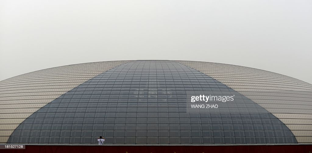 A man takes a photo in front of the China National Grand Theater in Beijing on September 22 2013 The sevenday holiday built around China's National...