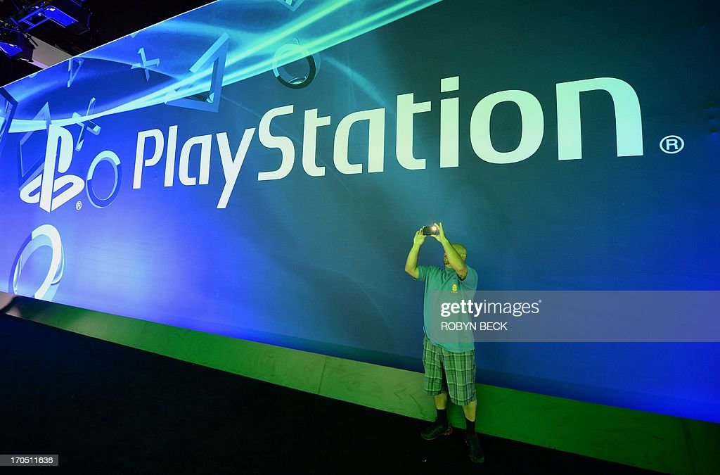 A man takes a photo in front of the PlayStation logo on the final day of the E3 Electronic Entertainment Expo, in Los Angeles, California June 13, 2013. AFP PHOTO / ROBYN BECK