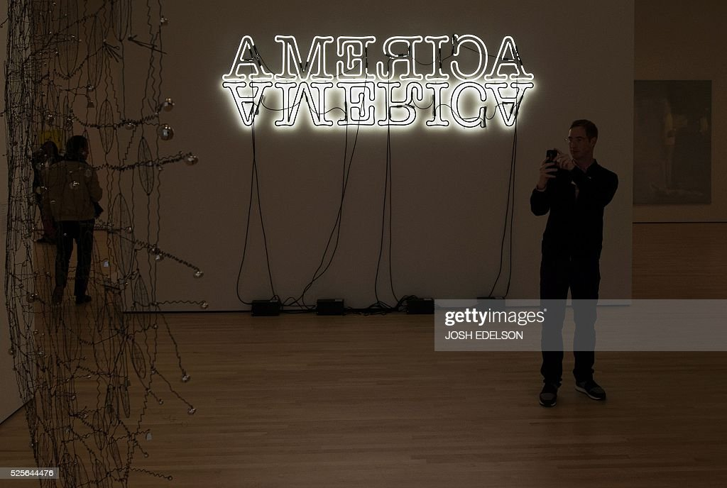 A man takes a photo near an art piece entitled 'Double America' inside the San Francisco Museum of Modern Art (SFMOMA) in San Francisco, California on April 28, 2016. The newly redesigned museum integrates a 10-story expansion in a new building and will open to the public on May 14, 2016. / AFP / Josh Edelson / RESTRICTED