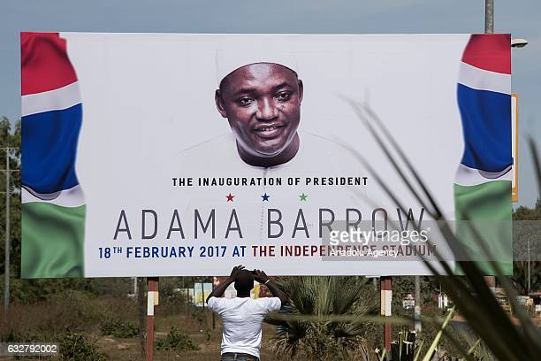 A man takes a photo of a billboard prepared for an invitation of the event which will be held at Independence Stadium on February 18 for Gambia's...